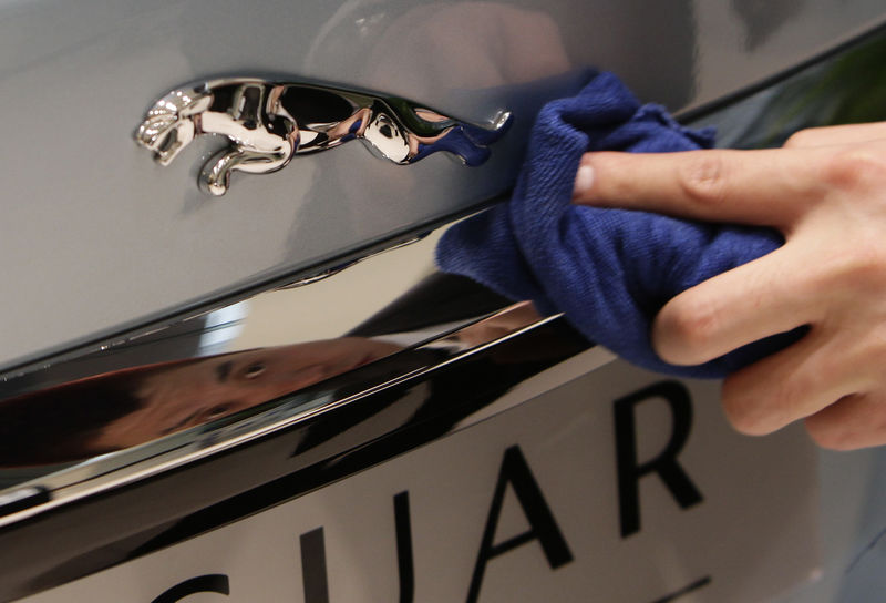 © Reuters. An employee cleans the logo of a Jaguar XJ car at a dealership in Beijing